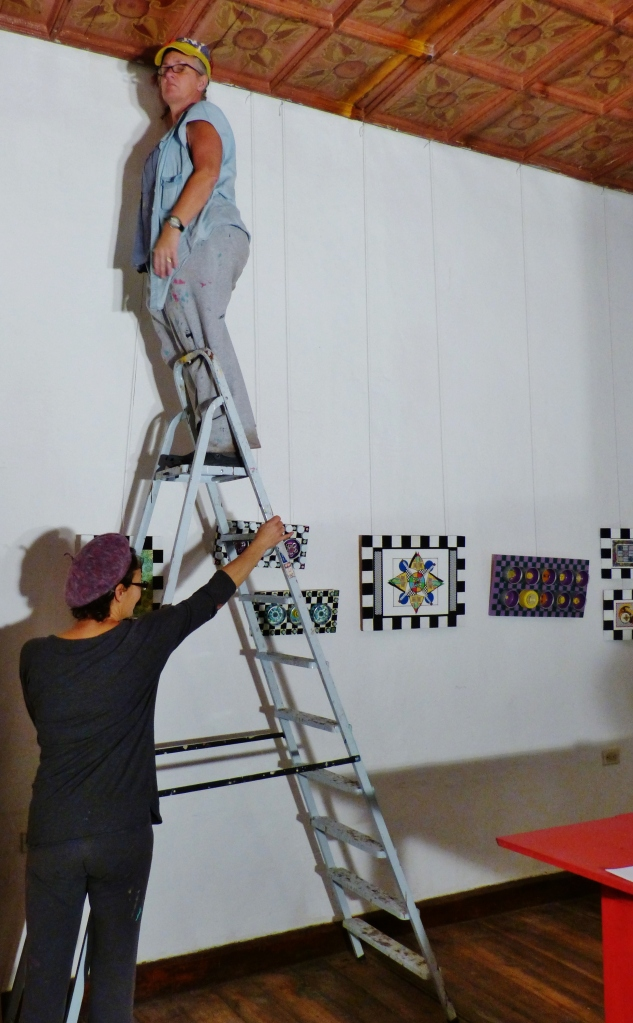 Kathy hanging her art for an exhibit at friend Laura's (holding ladder) creative space called Fishbon del Sur-