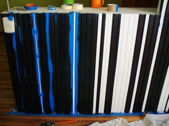 Taping to create stripes on one studio wall--